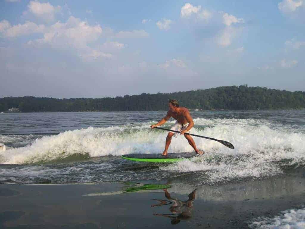 Jimmy Lewis Striker surf sup on bow wave of boat uk